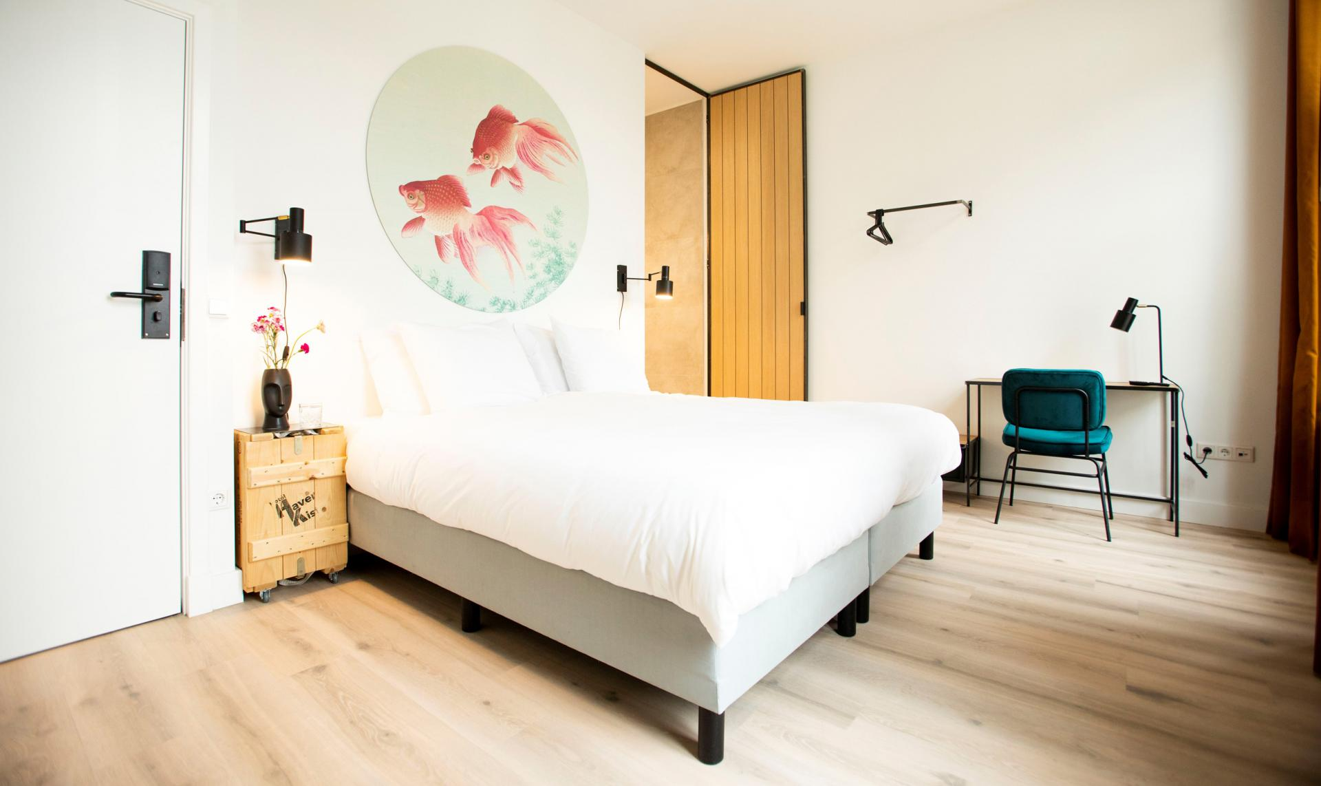 Light hotel room with wooden elements, a kingsize bed, a desk, that has a view on the heart of Den Bosch