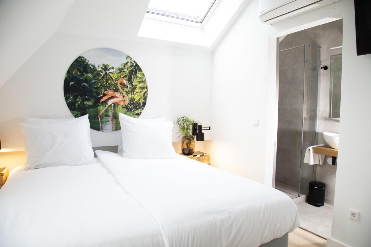 A light hotel room with a skylight, a small modern bathroom and a view on the city of Den Bosch