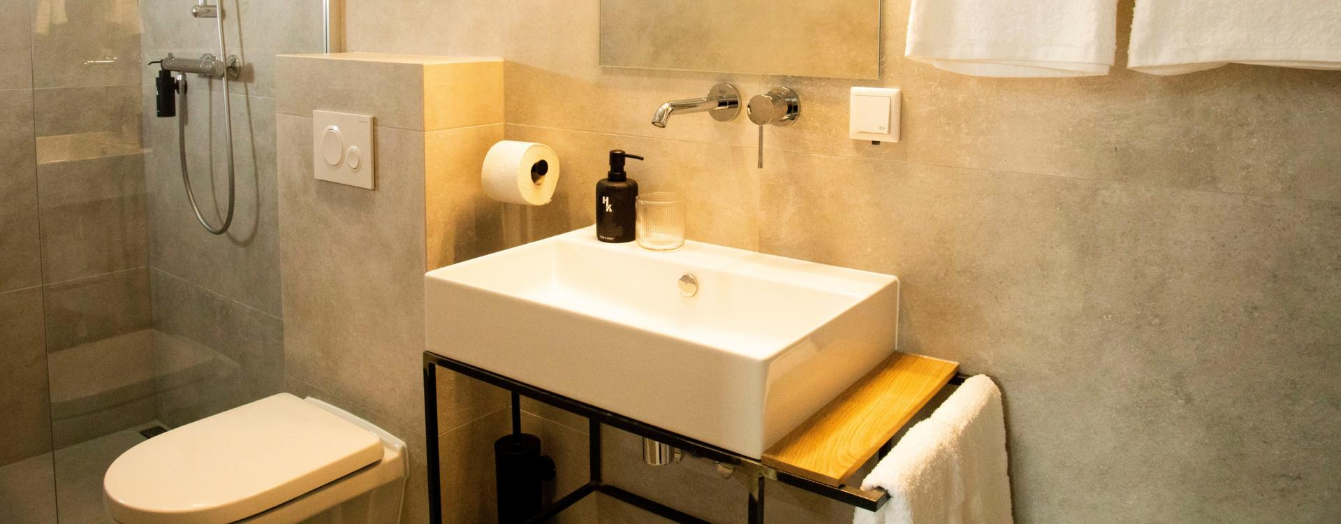 A modern bathroom with big grey tiles, a square sink, a toilet and white towels